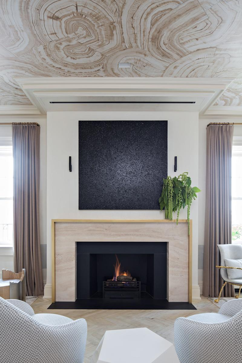 """The main living room of a Greenwich Village residence with a Jerusalem stone fireplace, surrounded in brass, below Yayoi Kusama's """"Infinity-Nets [Psst]"""" (2011), a pair of Gino Sarfatti sconces, and a ceiling painted with a tonal malachite pattern."""