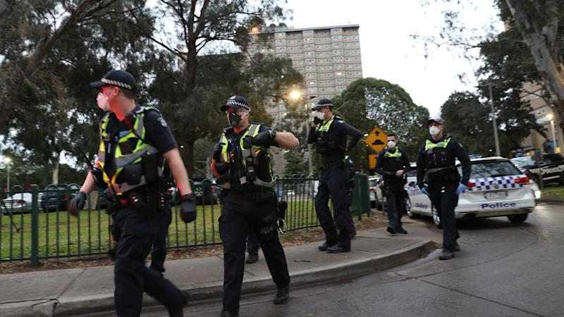 Source: Police are seen enforcing a lockdown at public housing towers on Racecourse Road in Flemington, Melbourne. Source: AAP