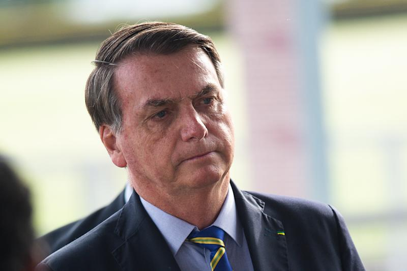 BRASILIA, BRAZIL - May 06: Brazilian President Jair Bolsonaro talks with supporters during amidst on the coronavirus (COVID-19) pandemic at the Palácio do Alvorada on May 06, 2020 in Brasilia. Brazil has over 114,000 confirmed positive cases of Coronavirus and 7,921 deaths. (Photo by Andressa Anholete/Getty Images)