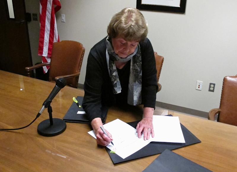 Liquor Control Board chairwoman Sharon Foster signs the rules to implement Washington state's new legal marijuana law, on Wednesday, Oct. 16, 2013, in Olympia, Wash. Washington became the second U.S. state to adopt rules for the recreational sale of marijuana Wednesday, setting what advocates hope will become a template for the legalization of the drug around the world. (AP Photo/Rachel La Corte)