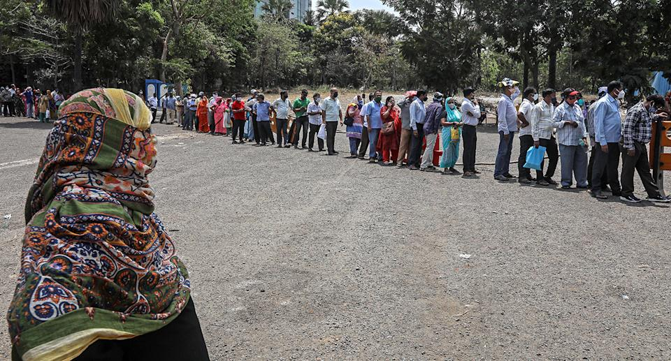People queue as they wait to receive a shot of COVID-19 vaccine at a vaccination centre in Mumbai, India.