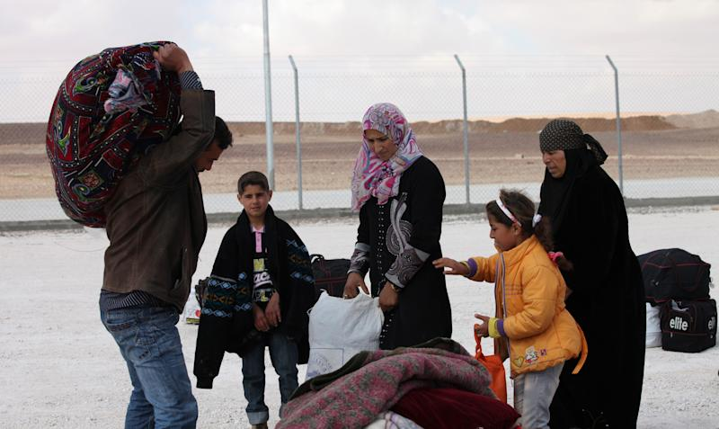 A newly-arrived Syrian refugee family carries their belongings at the new Jordanian-Emirati refugee camp, Mrajeeb al-Fhood, in Zarqa, Jordan, Wednesday, April 10, 2013. A second camp for Syrian refugees has opened in Jordan as more Syrians flee the civil war at home. The Jordanian-Emirati camp is the first funded by the United Arab Emirates and run by its Red Crescent Society in Jordan to assist families, single women, the disabled, and elderly.(AP photo/Mohammad Hannon)