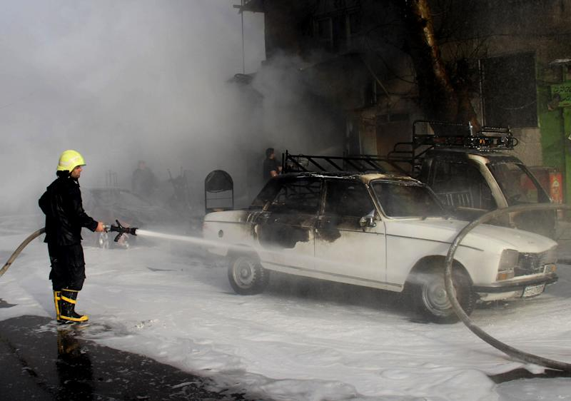 In this photo released by the Syrian official news agency SANA, a Syrian firefighter extinguishes a burned car at the scene where two mortar rounds exploded near an orphanage, at al-Boukhtyar area, in Damascus, Syria, Wednesday, March 13, 2013. The state-run SANA news agency said two mortar rounds exploded near an orphanage in al-Boukhtyar area, killing and wounding an unknown number of people. Syrian government troops fought fierce battles with rebels on Wednesday for control of key neighborhoods in the north of Damascus, residents and activists said. (AP Photo/SANA)