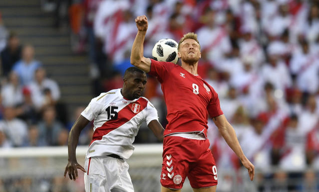 <p>Keep your eye on the ball! Peru's Christian Ramos, left, heads for the ball with Denmark's Nicolai Jorgensen.(AP) </p>
