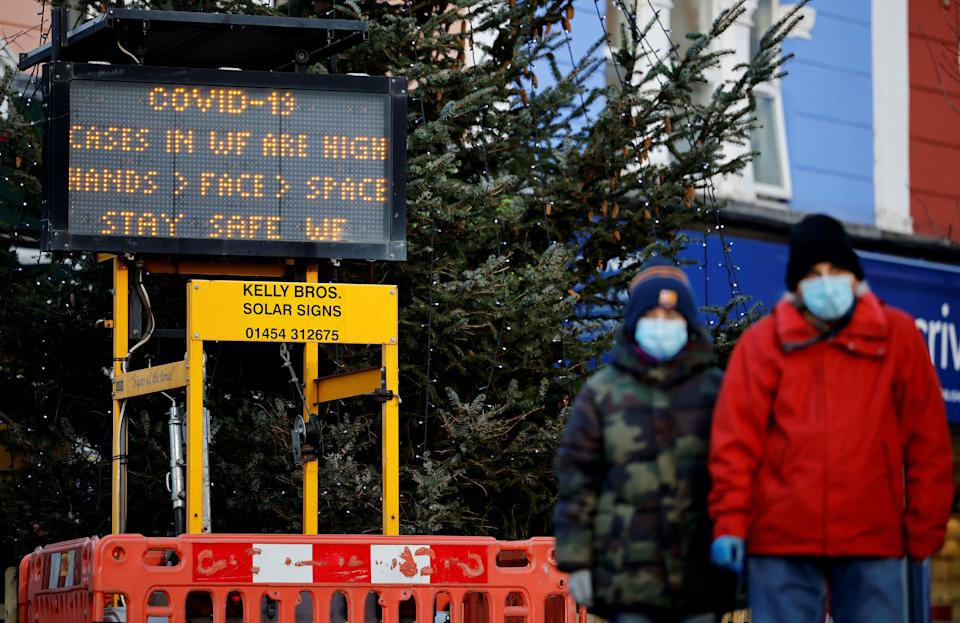 "Pedestrians wearing a face mask or covering due to the COVID-19 pandemic, walk past an electronic COVID-19 information sign in Walthamstow in north east London, on December 15, 2020. - Two leading British medical journals urged the government Tuesday to scrap plans to ease coronavirus restrictions over Christmas, warning it would be ""another major error that will cost many lives"". The British capital faces tougher Covid-19 measures within days, the UK government said on Monday, with a new coronavirus variant emerging as a possible cause for rapidly rising infection rates. (Photo by Tolga Akmen / AFP) (Photo by TOLGA AKMEN/AFP via Getty Images)"