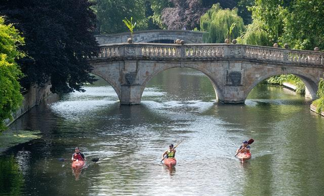 People kayak along the River Cam in Cambridge