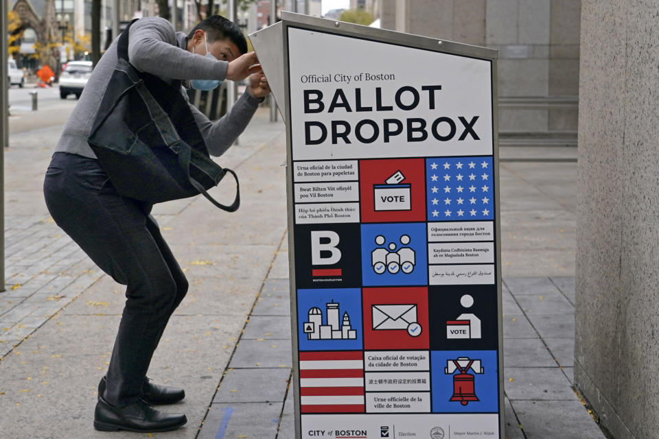 "A voter makes sure his ballot falls into the ballot drop box outside the Boston Public Library, Monday, Oct. 26, 2020, in Boston. Massachusetts election officials say a fire was set in the ballot drop box Sunday, holding more than 120 ballots in what appears to have been a ""deliberate attack."" The FBI says it is investigating. (AP Photo/Elise Amendola)"