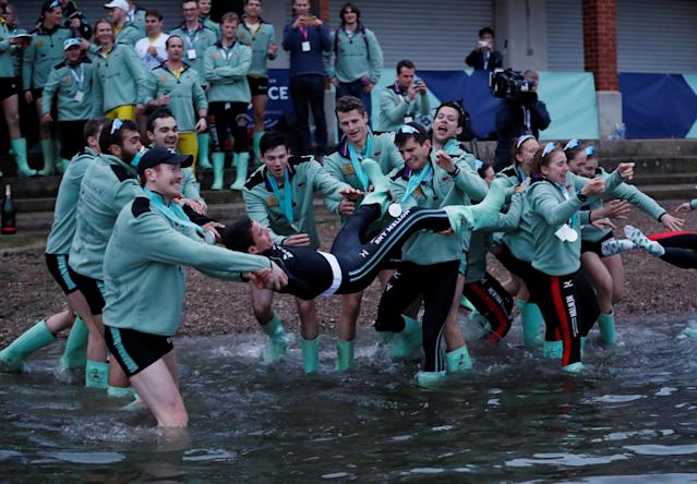Rowing - 2018 Oxford University vs Cambridge University Boat Race - London, Britain - March 24, 2018 Cambridge men's Cox Hugo Ramambason is thrown in the river as they celebrate winning the boat race REUTERS/Peter Cziborra