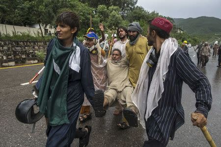 Supporters of Tahir ul-Qadri, a Sufi cleric and leader of Pakistan Awami Tehreek (PAT) party, help a fellow supporter who is injured, during the Revolution March in Islamabad September 1, 2014. REUTERS/Zohra Bensemra
