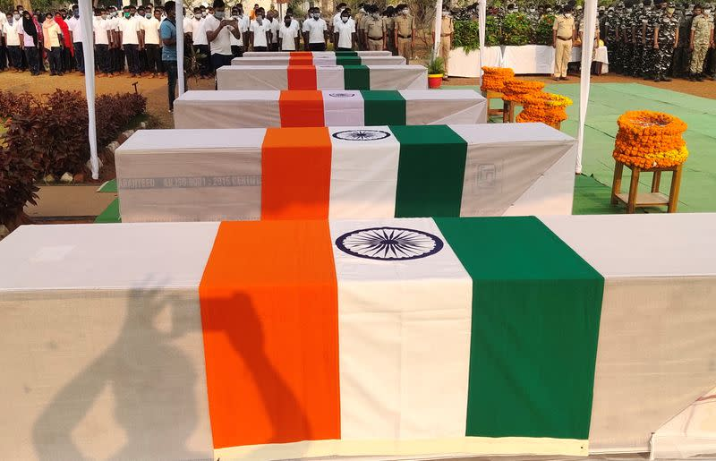 Security force personnel pay homage next to the coffins of their colleagues who were killed in an attack by Maoist fighters, during a wreath laying ceremony in Bijapur