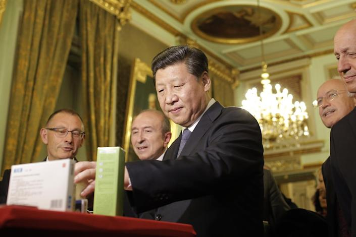 Chinese President Xi Jinping looks at local products during a visit before a dinner at the town hall in Lyon, central France, Tuesday, March 25, 2014. Xi Jinping arrived in France for a three-day state visit. (AP Photo/Laurent Cipriani, Pool)