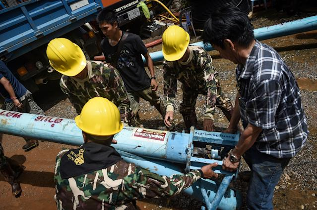 <p>Technicians lift water pumps to the drilling site near Tham Luang Cave in Chiang Rai Province on July 1, 2018, as the rescue operation continues for a missing children's soccer team and their coach. (Photo:Lillian Suwanrumpha/AFP/Getty Images) </p>