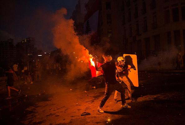A protestor throws a burning flare at Internal Security Forces, not pictured, during a protest at Martyrs Square in Beirut, Lebanon.