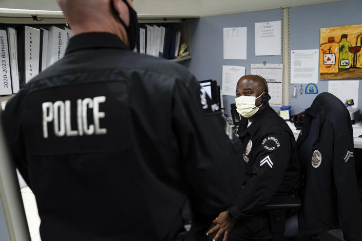 In this Sept. 9, 2020, photo Los Angeles Police recruitment officers, Dion Gourdine, right, and Christopher Hoffman, chat in the office in Los Angeles. (AP Photo/Jae C. Hong)