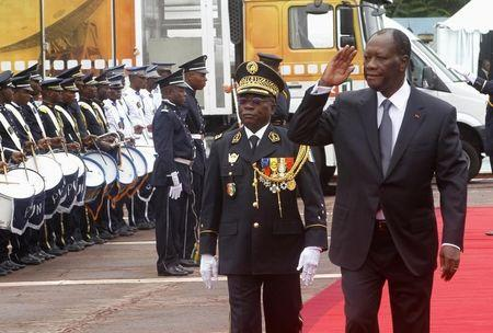 Ivory Coast's President Ouattara walks next to Chief of Staff, General Bakayoko during a parade to commemorate the country's 54th Independence Day, outside the presidential palace in Abidjan