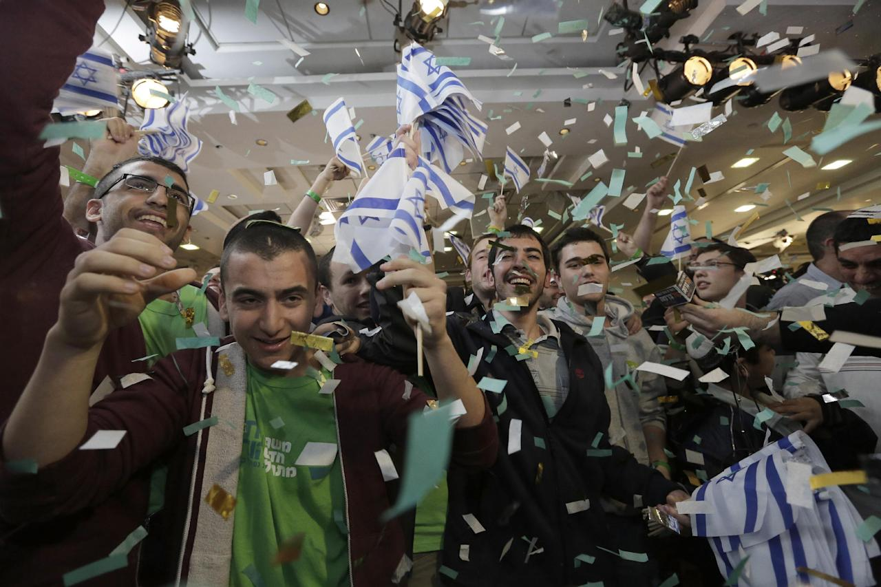 Supporters of Naftali Bennett, head of Israel's Jewish Home party celebrate after the exit polls were announced at the party's headquarters in the city of Ramat Gan, Tuesday, Jan. 22, 2013. Israeli Prime Minister Benjamin Netanyahu's Likud Party emerged as the largest faction in a hotly contested parliamentary election on Tuesday, positioning the hard-liner to serve a new term as prime minister, according to exit polls. But a lackluster performance by Likud, along with surprising gains by a centrist newcomer, raised the strong possibility that he will be forced to form a broad coalition. (AP Photo/Tsafrir Abayov)