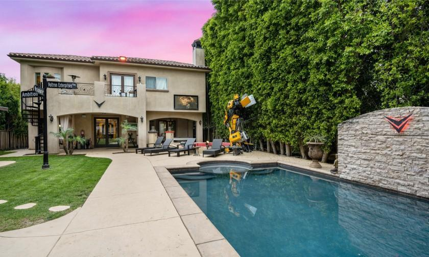 The Mediterranean-style property includes a backyard with a movie screen, swimming pool, street sign and giant Transformers replica.