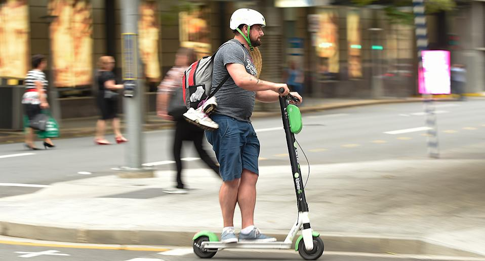 A Lime user crosses the street in a scooter around the Brisbane CBD