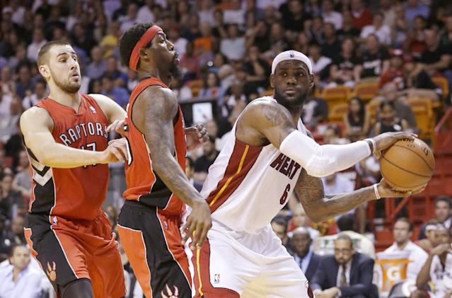 Miami Heat forward LeBron James (6) looks for an open teammate past Toronto Raptors center Jonas Valanciunas (17) of Lithuania, and forward John Salmons (25) during the first half of an NBA basketball game, Monday, March 31, 2014 in Miami. (AP Photo/Wilfredo Lee)