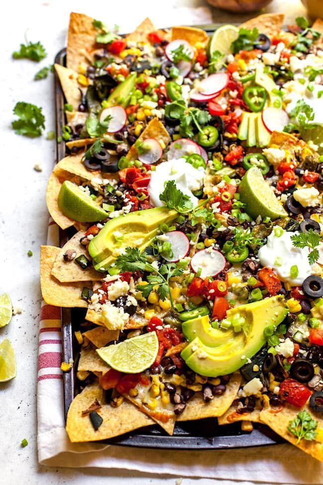 "<p>Feed a big crowd with these loaded nachos topped with black beans, charred corn, and fresh avocado.</p><p><strong>Get the recipe at <a href=""https://www.twopeasandtheirpod.com/charred-corn-poblano-black-bean-nachos/"" rel=""nofollow noopener"" target=""_blank"" data-ylk=""slk:Two Peas and Their Pod"" class=""link rapid-noclick-resp"">Two Peas and Their Pod</a>.</strong></p><p><strong><a class=""link rapid-noclick-resp"" href=""https://www.amazon.com/Nordic-Ware-Natural-Aluminum-Commercial/dp/B0049C2S32/?tag=syn-yahoo-20&ascsubtag=%5Bartid%7C10050.g.2966%5Bsrc%7Cyahoo-us"" rel=""nofollow noopener"" target=""_blank"" data-ylk=""slk:SHOP BAKING SHEETS"">SHOP BAKING SHEETS</a><br></strong></p>"