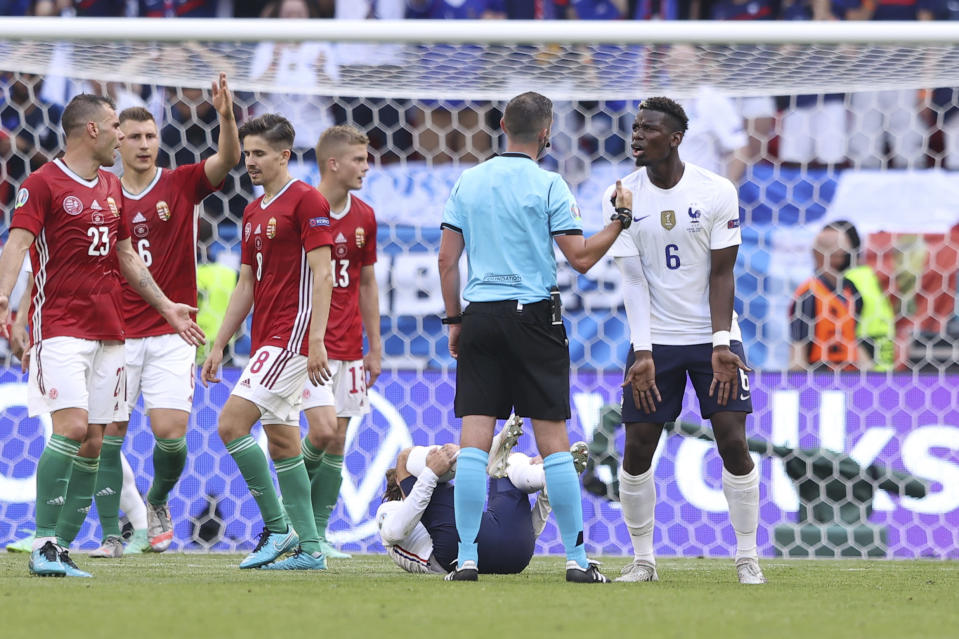France's Paul Pogba takes on British referee Michael Oliver during the Euro 2020 soccer championship group F match between Hungary and France, at the Ferenc Puskas stadium, in Budapest, Saturday, June 19, 2021. (Alex Pantling, Pool via AP)
