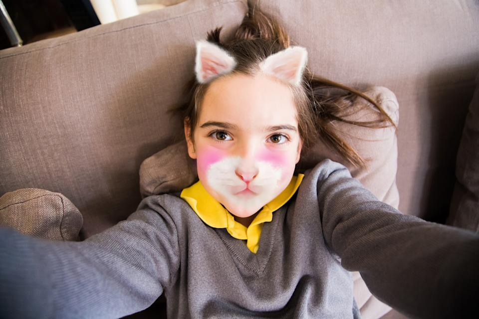 Little girl taking a selfie with smartphone on the home living room having fun using colorful filters applications changing her face like a cute kitten.