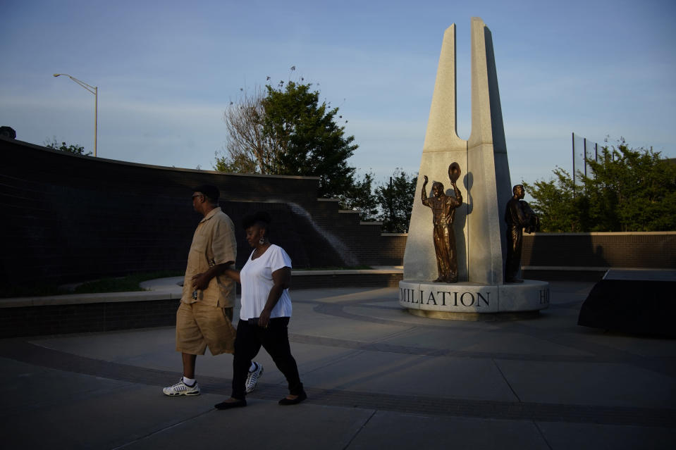 """Demetrius Boyd, left, and Loretta Boyd walk by a sculpture recognizing the Tulsa Race Massacre at the John Hope Franklin Reconciliation Park, Wednesday, May 26, 2021, in Tulsa, Okla. The two, from Tulsa, visited the park memorializing the Tulsa Race Massacre ahead of the 100 year anniversary. """"History and education, and you have a sense of calmness and peace,"""" said Demetrius Boyd about visiting the park for the first time. (AP Photo/John Locher)"""
