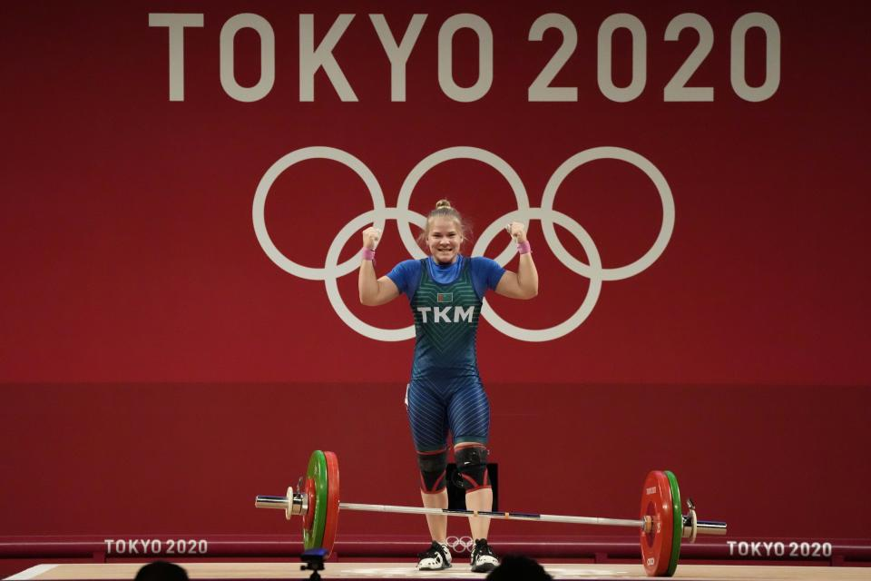 Polina Guryeva of Turkmekistan celebrates after a lift as she competes in the women's 59kg weightlifting event, at the 2020 Summer Olympics, Tuesday, July 27, 2021, in Tokyo, Japan. (AP Photo/Luca Bruno)