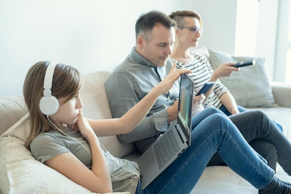 young girl using laptop on bed while mom and dad watching TV and not paying attention to her
