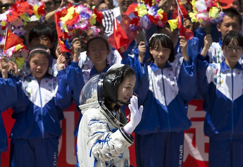 Chinese students wave flowers and national flags as female astronaut Wang Yaping leaves the Jiuquan satellite launch center for the launch site, near Jiuquan in western China's Gansu province, Tuesday, June 11, 2013. Three Chinese astronauts will take flight on Tuesday evening if weather permits, aboard the spacecraft to the dock with China's Tiangong 1 space lab. (AP Photo/Andy Wong)