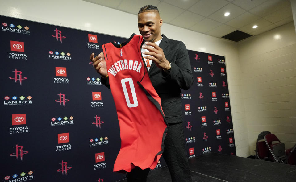 Recently acquired Houston Rockets' guard Russell Westbrook grabs his jersey after a news conference, Friday, July 26, 2019, in Houston. Westbrook was acquired from the Oklahoma City Thunder.