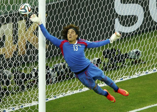 Mexico's Ochoa jumps to save the ball during their 2014 World Cup Group A soccer match against Brazil at the Castelao arena in Fortaleza