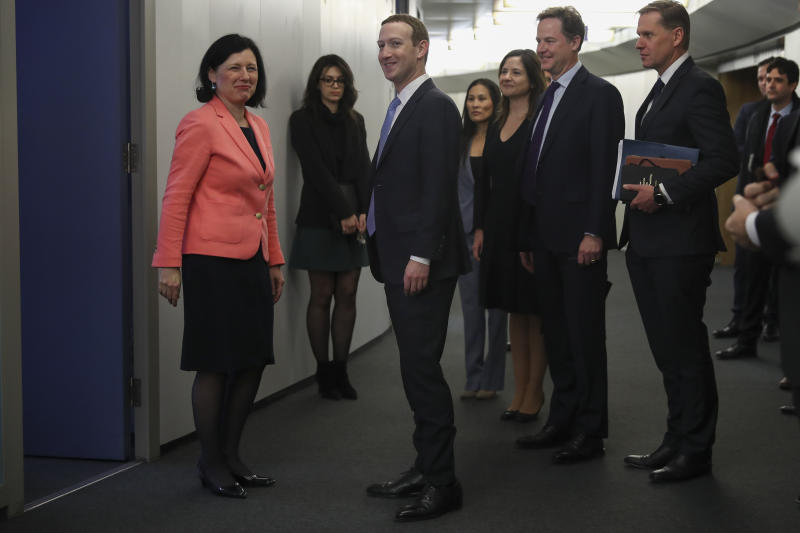 Facebook CEO Mark Zuckerberg, center, is greeted by European Commissioner for Values and Transparency Vera Jourova, left, prior to a meeting at EU headquarters in Brussels, Monday, Feb. 17, 2020. (AP Photo/Francisco Seco)