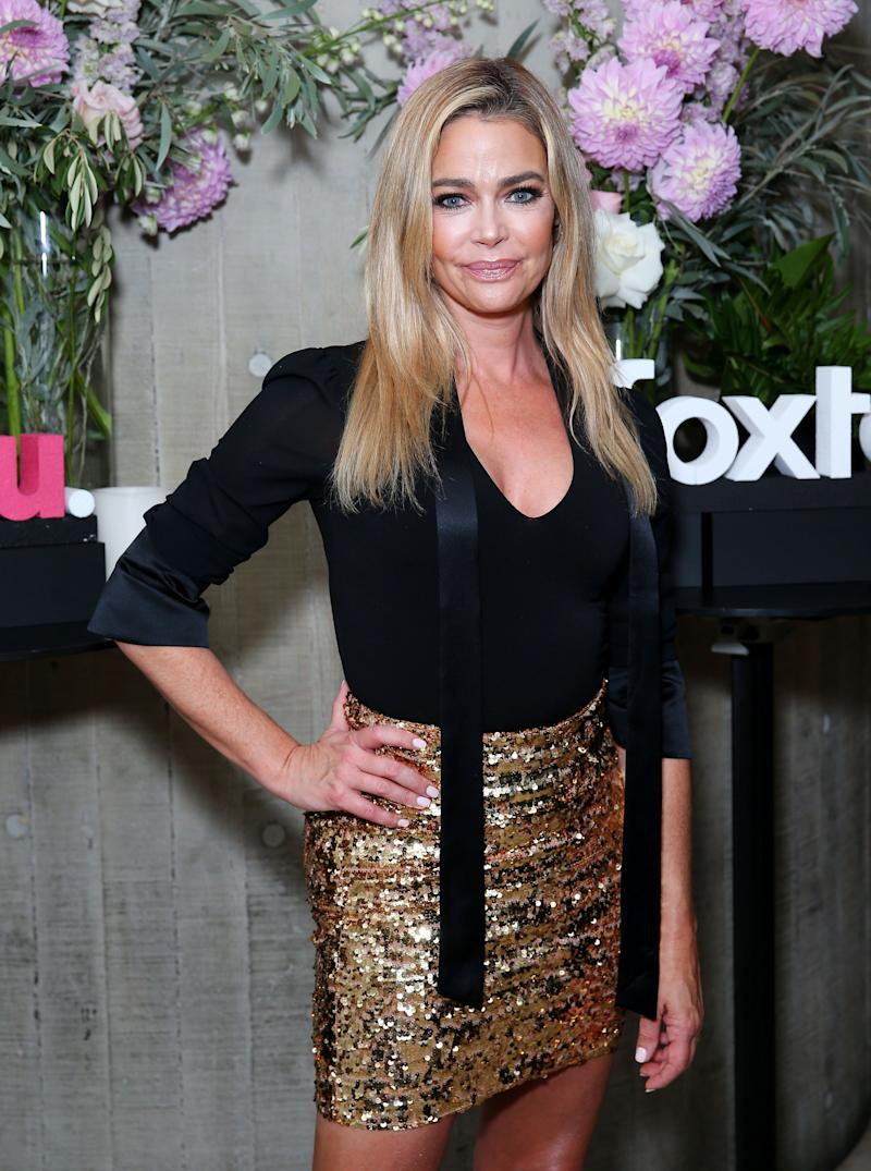 Denise Richards sports a black dress with body-con skirt, leaving her amazing skin on display