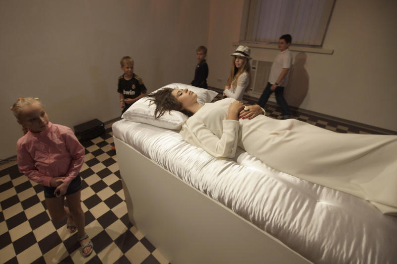 Young visitors looks on a new art project called 'Sleeping Beauties' created by a Canadian-Ukrainian artist Taras Polataiko in The National Art Museum in Kiev, Ukraine, Friday, Sept. 7, 2012. Five young Ukrainian women, dressed in white wedding gowns, take turns sleeping on display in the museum for a couple of hours every day. Based on the fairytale 'Sleeping Beauty', the idea of the art-exhibition is for visitors to look at a sleeping girl, and, if they feel the urge, kiss her on the lips. If a sleeping beauty opens up her eyes she's obliged by a legal contract to marry. (AP Photo/Efrem Lukatsky)