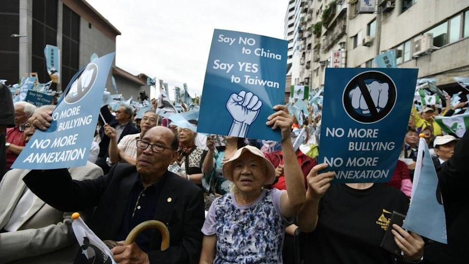 Pro-independence activists hold signs at a demonstration in Taipei on 20 October 2018