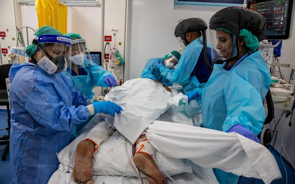 Staff in the unit 'proning' a patient. Lying face down helps oxygenate the blood which in turn assists with combatting respiratory distress. - Heathcliff O'Malley for the Telegraph