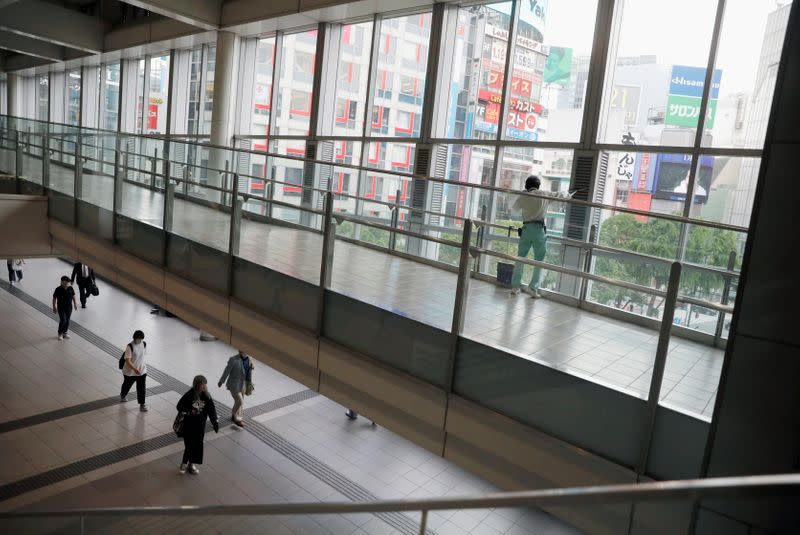 People wearing protective face masks walk at Shibuya station as the spread of the coronavirus disease (COVID-19) continues, in Tokyo
