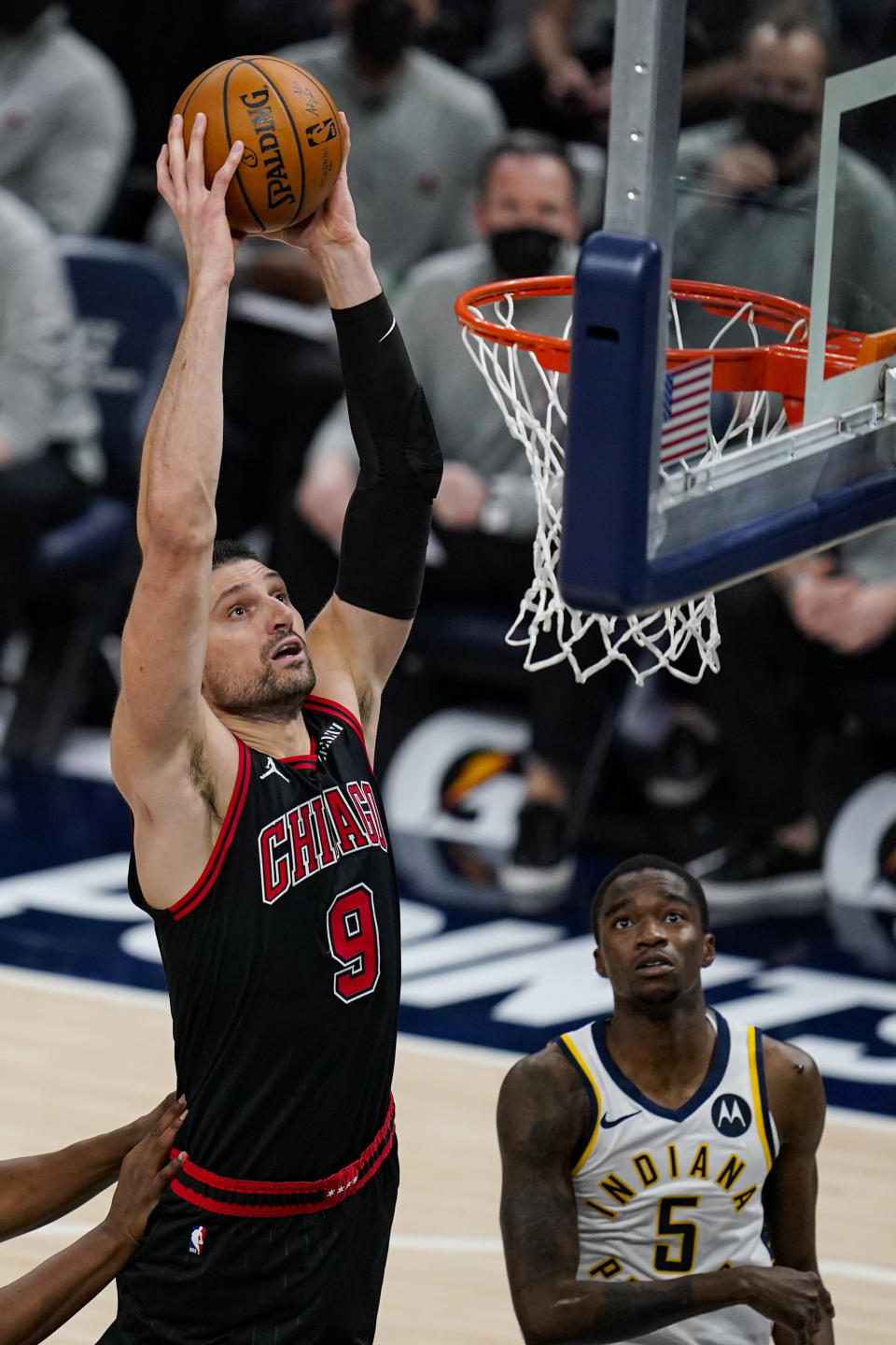 Chicago Bulls center Nikola Vucevic (9) dunks over Indiana Pacers guard Edmond Sumner (5) during the second half of an NBA basketball game in Indianapolis, Tuesday, April 6, 2021. (AP Photo/Michael Conroy)