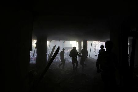 Palestinians run inside a building that was hit by an Israeli air strike, in the southern Gaza Strip May 5, 2019. REUTERS/Ibraheem Abu Mustafa