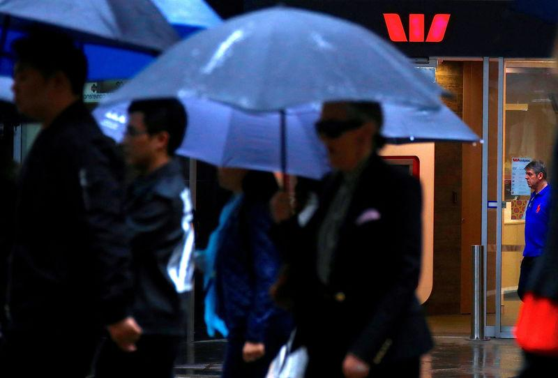 FILE PHOTO: Pedestrians hold umbrellas as they walk past a branch of the Westpac Banking Corp in central Sydney, Australia