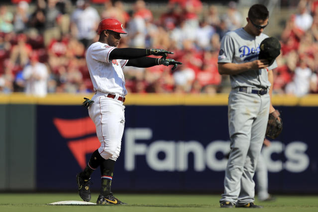 Cincinnati Reds' Yasiel Puig, left, reacts at second base after hitting a two-run single in the third inning of a baseball game against the Los Angeles Dodgers, Saturday, May 18, 2019, in Cincinnati. (AP Photo/Aaron Doster)