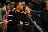 <p>Teigen rests her head against her husband while watching the Los Angeles Lakers basketball game at the city's Staples Centre.</p>