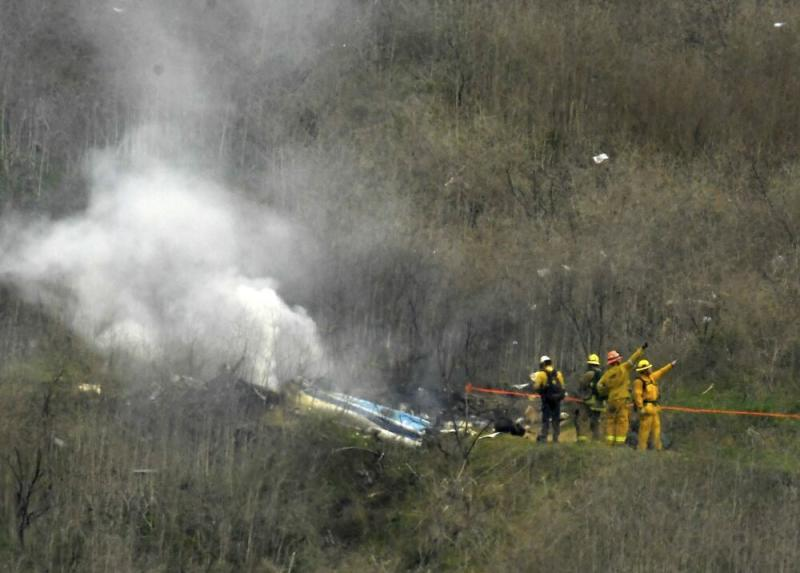 Firefighters working at the scene of the helicopter crash | Shutterstock