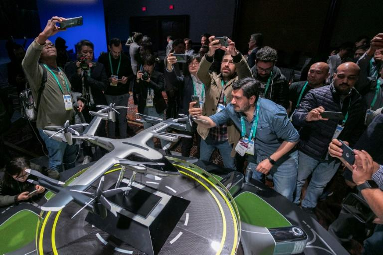 People take photos of a model of Hyundai's S-A1 electric vertical takeoff and landing (eVTOL) aircraft built in partnership with Uber to create an air taxi network, during the 2020 Consumer Electronics Show (CES) in Las Vegas