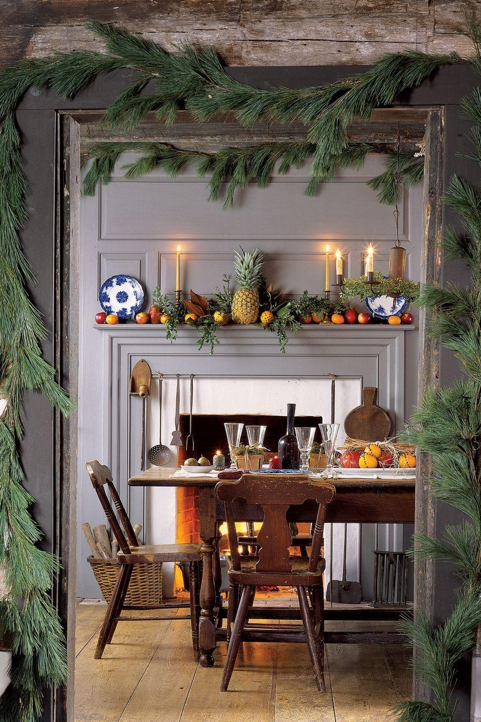"<p>Evocative and soothing, candlelight creates the right ambience for the holidays. Lit candles are more than decorative objects, highlighting seasonal festivities and fostering a celebratory mood. Garlands around the door frame beckon guests into the room, and on the mantel sits a pineapple, an early-American symbol of hospitality.</p><p><a class=""link rapid-noclick-resp"" href=""https://www.amazon.com/s/ref=nb_sb_noss_1?url=search-alias%3Daps&field-keywords=garlands&rh=i%3Aaps%2Ck%3Agarlands&tag=syn-yahoo-20&ascsubtag=%5Bartid%7C10050.g.644%5Bsrc%7Cyahoo-us"" rel=""nofollow noopener"" target=""_blank"" data-ylk=""slk:SHOP GARLAND"">SHOP GARLAND</a></p>"