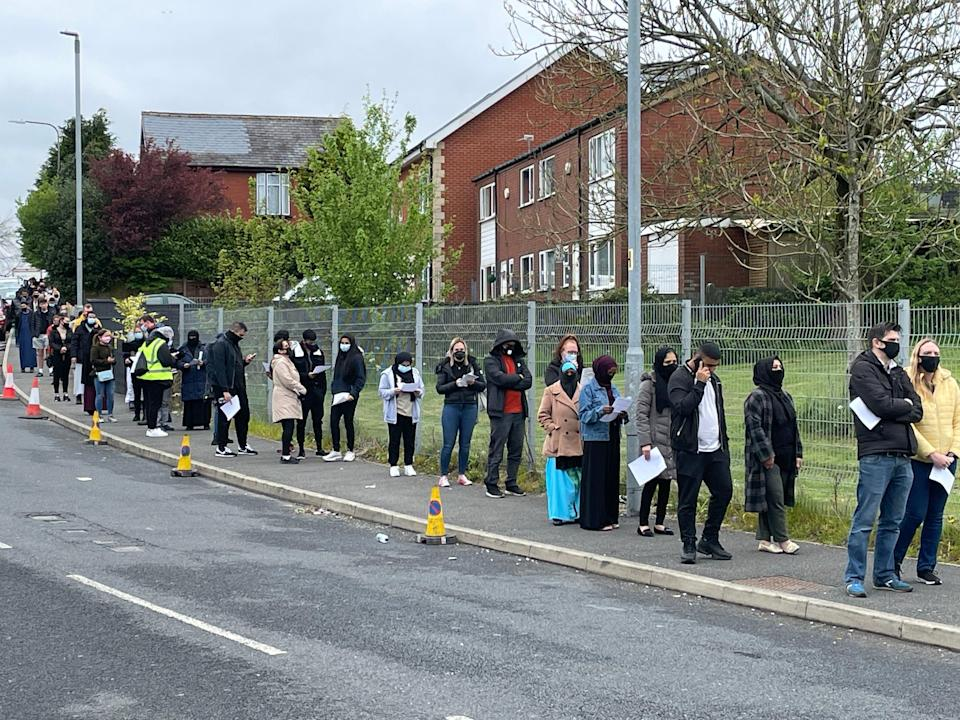 <p>People queue for the vaccination centre at the Essa Academy in Bolton, where the Indian variant has been detected</p> (PA)