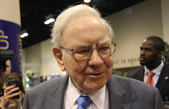 Warren Buffett smiles at someone as he walks through a crowd at a conference.