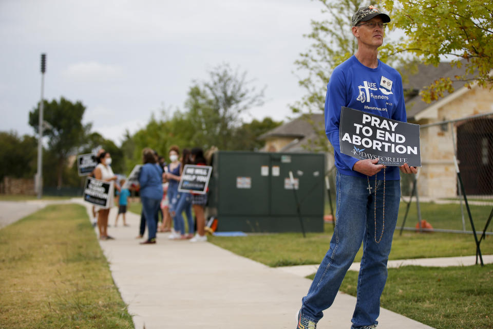 Timothy Dougherty and about a dozen other anti-abortion demonstrators protest outside of a Whole Women's Health of North Texas, Friday, Oct. 1, 2021, in McKinney, Texas. A federal judge did not say when he would rule following a nearly three-hour hearing in Austin during which abortion providers sought to block the nation's most restrictive abortion law, which has banned most abortions in Texas since early September. (AP Photo/Brandon Wade)