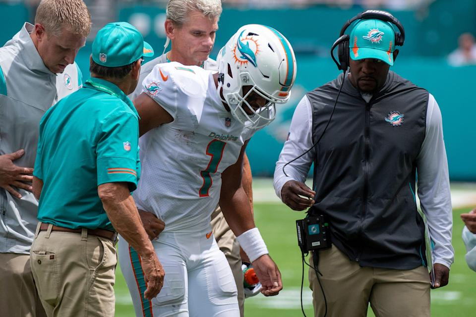 Miami Dolphins quarterback Tua Tagovailoa (1) is helped off of the field with a rib injury along with Miami Dolphins head coach Brian Flores (right) during an NFL football game against the Buffalo Bills, Sunday, Sept. 19, 2021, in Miami Gardens, Fla.